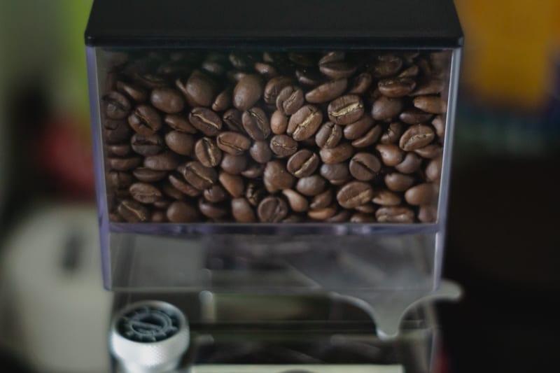 Kaffeelehrling arbeitet mit Mühle